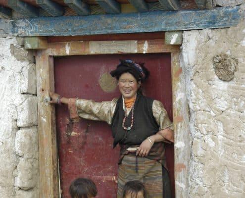 Tibetansk familie foran deres hus