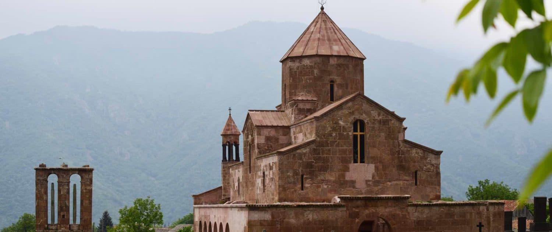 Odzun Kloster med bjerglandskab i baggrunden