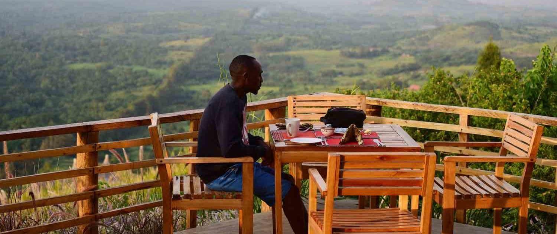 Mand spiser frokost med smuk udsigt i baggrunden