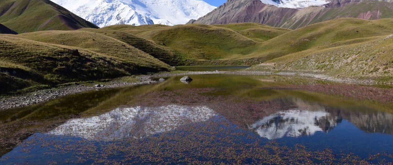Lille sø med bjerglandskab i baggrunden
