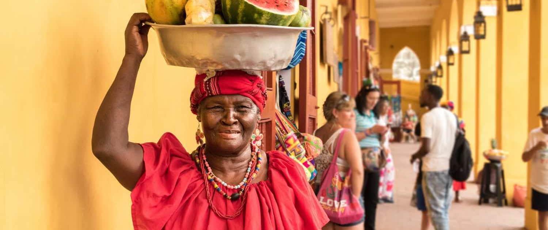 Kvinde bærer frugter på hovedet
