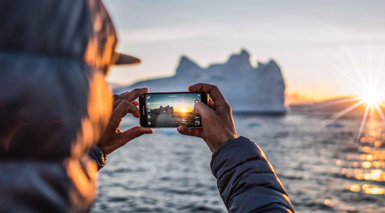 Telefon tager billede af den arktiske solopgang