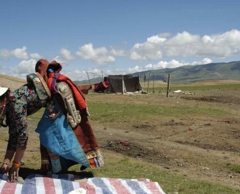 Nomadekvinde med teltskole i baggrunden