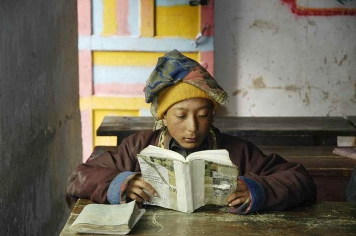 Nomadedreng læser lektier på skolen